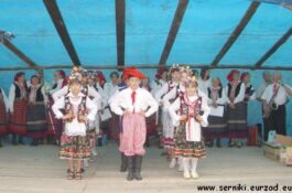 Obrazek przedstawiający tańczące dzieci ubrane w tradycyjne stroje